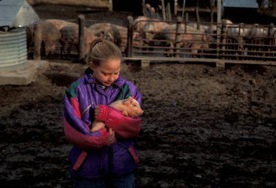 Photo: A girl holds a small pig near a muddy pig pen in Bennett, Nebraska.