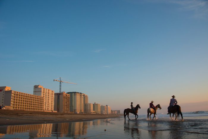 Photo: Cowboys on Virginia Beach at sunrise.