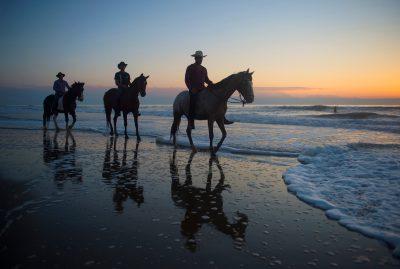 Photo: Cowboys on Virginia Beach at sunrise.