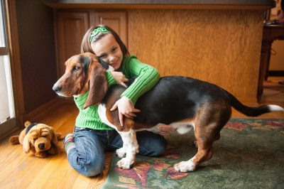 Photo: A girl hugs her basset hound in a Nebraska home.