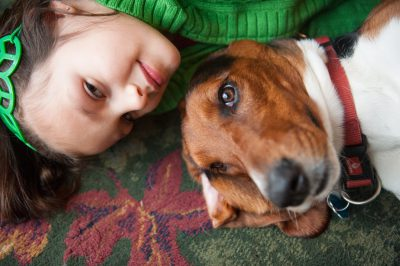 Photo: A girl lies on the floor with her basset hound in a Nebraska home.