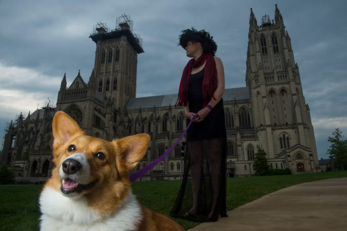 Photo: A woman and her dog in front of the National Cathedral, Washington, District of Columbia.