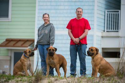 Photo: A man and woman with their three South African mastiffs at Virginia Beach, Virginia.