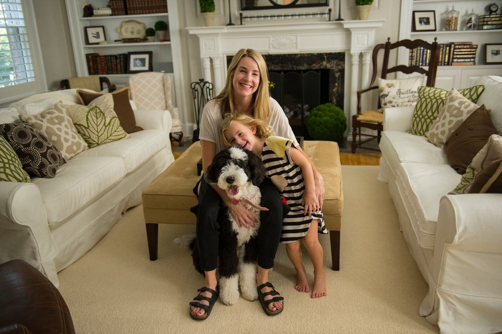 Photo: A woman plays with her daughter and the family dog.