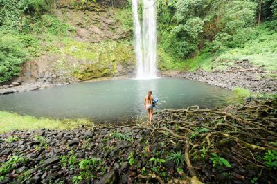 Photo: A woman approaches a pool below a waterfall on Bioko Island.