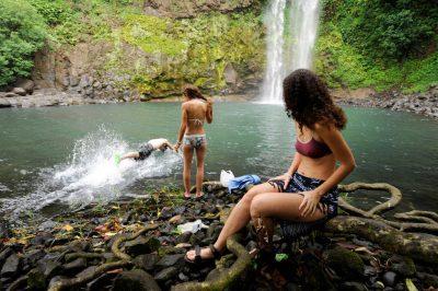 Photo: Young adults bathe in the pool below a waterfall on Bioko Island.