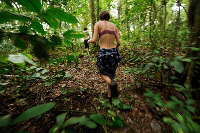 Photo: A woman moves quickly through a jungle on Bioko Island.