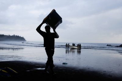 Photo: A man carries a box of equipment at the Moraka Playa on Bioko Island.