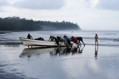 Photo: A crew pushes a boat to shore on Bioko Island.