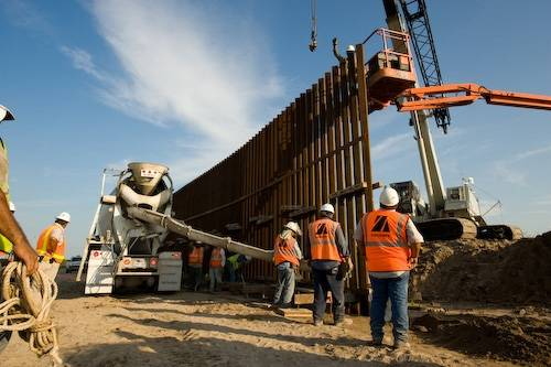 Photo: Mexican laborers constructing the border wall that separate the United States from Mexico near Alamo, Texas.