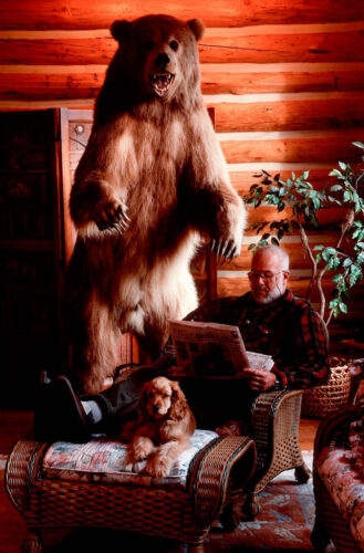 Photo: A Montana man relaxes in the evening with his dog and stuffed grizzly bear.