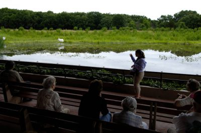 Photo: Visitors listen to a guide at the whooping crane exhibit at the International Crane Foundation.