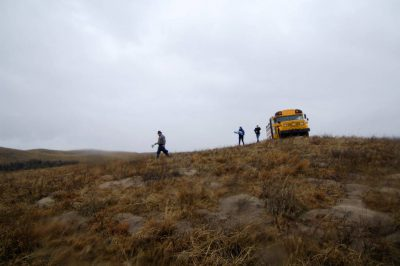Photo: A man leads fellow grouse watchers away from a school bus that's used as a sharp tail grouse viewing blind.
