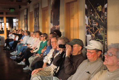Photo: Birdwatchers use binoculars to view cranes from a blind at Rowe Audubon Sanctuary in Nebraska.