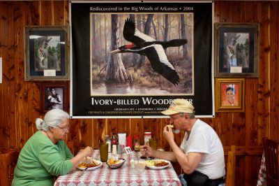 Photo: An elderly couple at a bar-b-que restaurant eating below a poster of the ivory-billed woodpecker in Brinkley, Arkansas.
