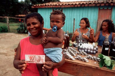 Photo: A villager displays the first profits from a medicinal plants workshop led by Patricia Shanley in the village of Quiandeua in the Brazilian Amazon.