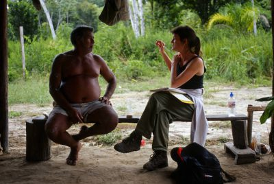 Photo: Patricia Shanley talks to landowner Mangueira about the value of forest fruits and medicinal plants in the Brazilian Amazon.
