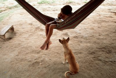 Photo: Daily life along the Capim River in the Brazilian Amazon: adog begs for scraps as a child eats lunch in a hammock.