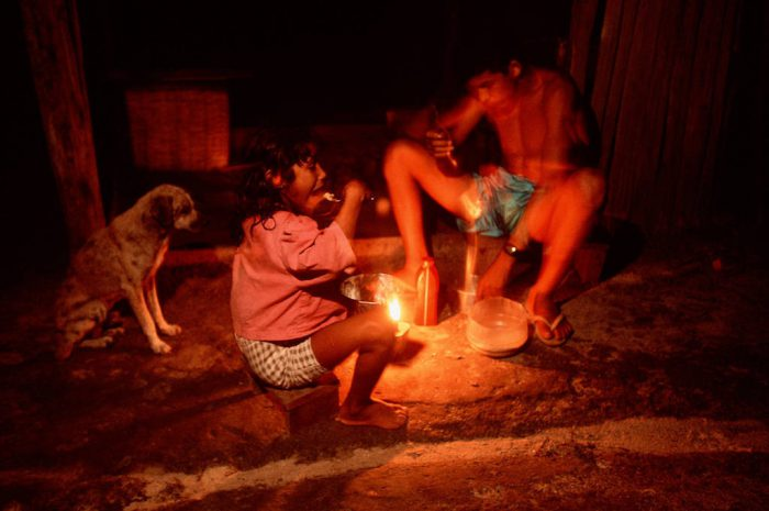 Photo: Daily life along the Capim River in Quiandera village: theevening meal is eaten from a dirt floor by candle light.