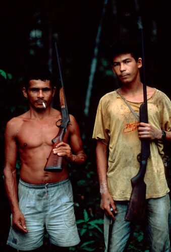 Photo: A local hunter/gatherer stands next to a friend in the forests of the Brazilian Amazon.