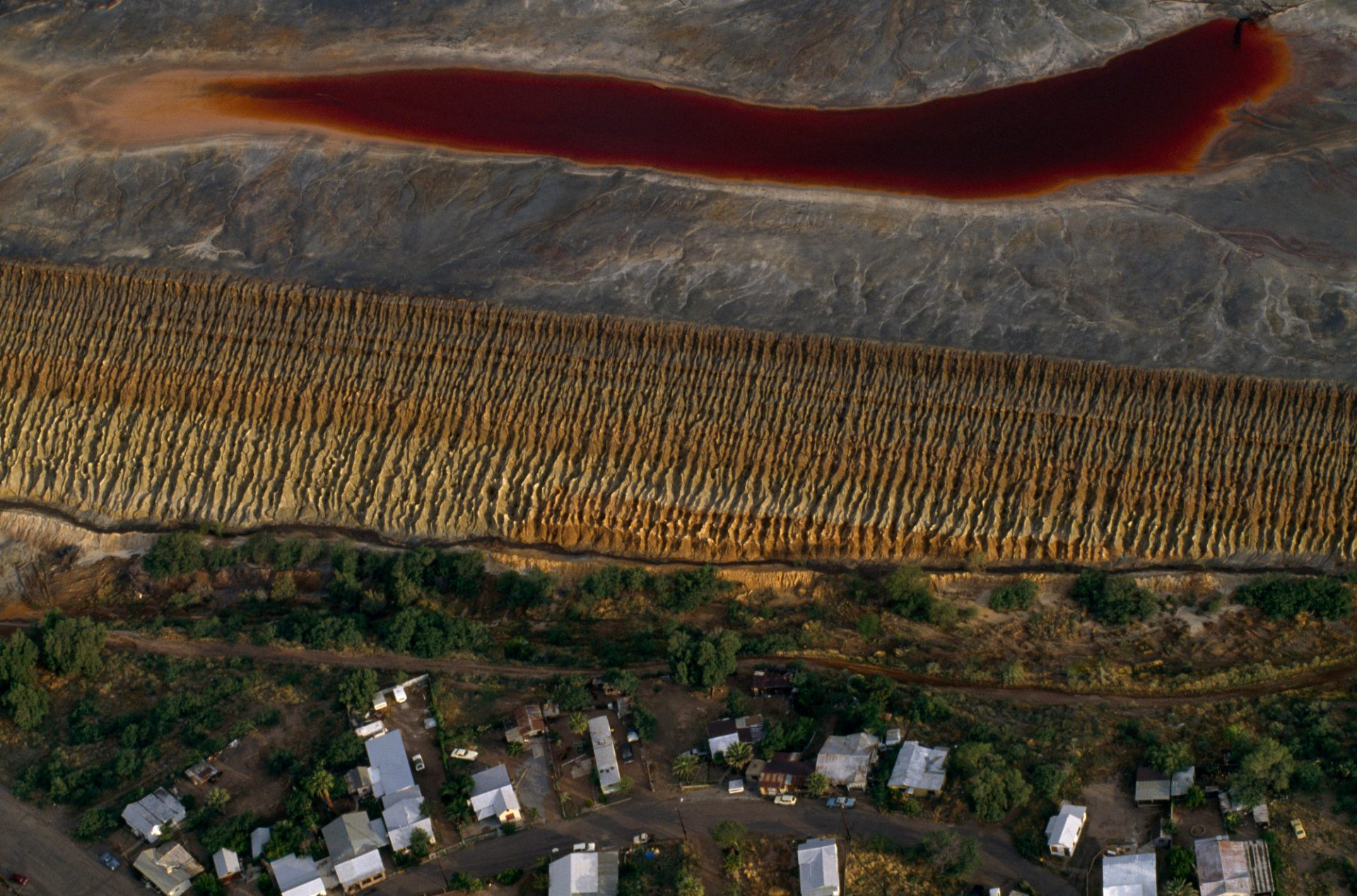 Photo: A copper-tailings impoundment next to a housing development in Arizona threatens leeching of chemicals into groundwater as seen in the sulfide-tinged pool of rainwater.