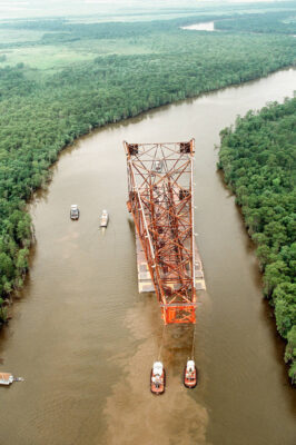 Photo: Barges tow an oil rig through the bayou country near Homa, LA.