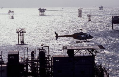 Photo: A helicopter moves from rig to rig in one of the most densely structured oil fields along the gulf coast of Louisiana.