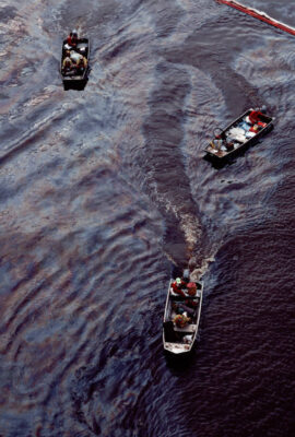 """Photo: Cleanup work on an oil spill in the Texas Intercoastal Canal, using a """"control boom""""."""