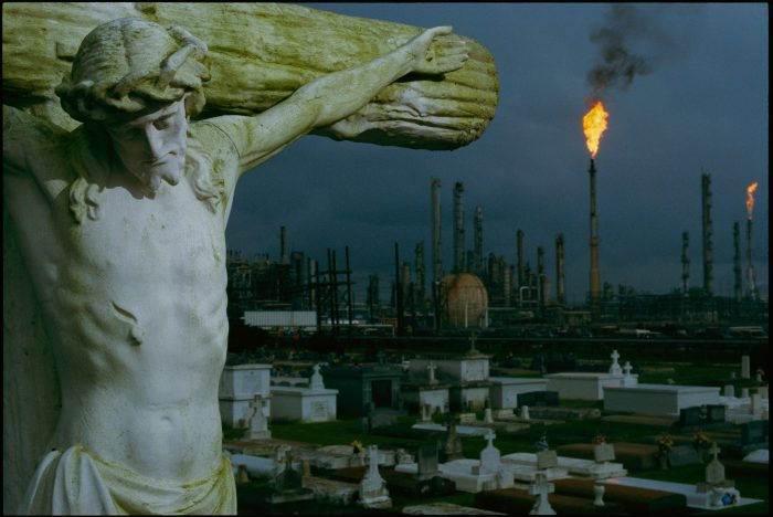 Photo: A crucifixion statue in Holy Rosary Cemetery overlooks petrochemical plants massed upriver from New Orleans to Baton Rouge, Louisiana.