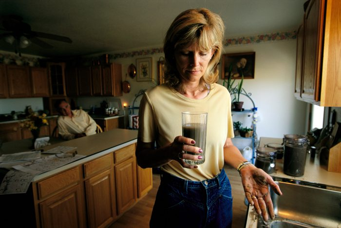 Photo: A homeowner in the powder river basin holds up a glass of water from a now unusable well.