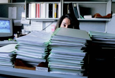 Photo: A legal instruments examiner for the Bureau of Land Management in Pinedale, Wyoming is shown behind a mountain of applications for permit to drill submitted by oil and gas companies.
