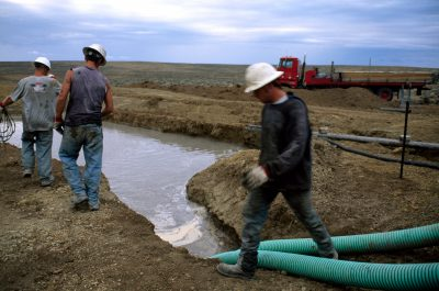 Photo: Workers observe water spilling from a gas well in Wyoming.
