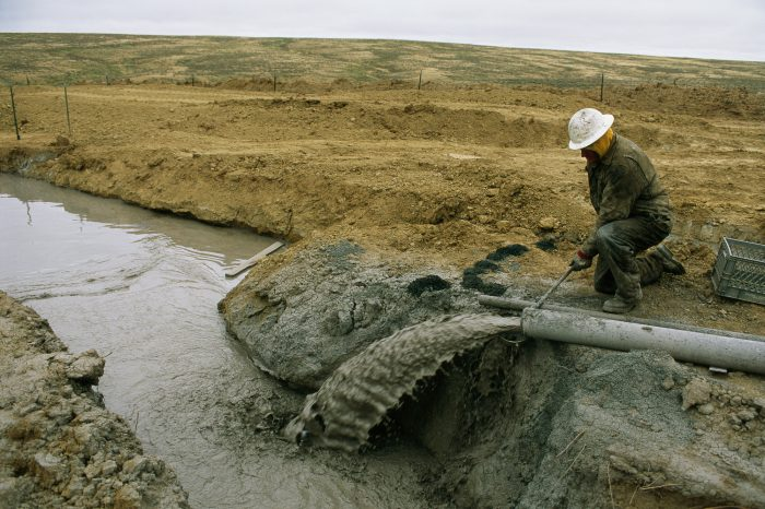 Photo: A worker samples water and drilling mud coming from a rig at a coal bed methane drill site near Buffalo, WY. The fluid goes to a pond and at this well, it is recirculated.