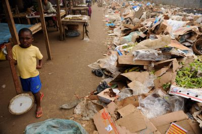 A boy stands near piles of trash at the edge of the market in Malabo, Equatorial Guinea, Africa.