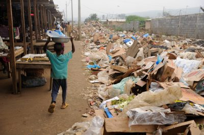 A boy carries water near piles of trash at the edge of the market in Malabo, Equatorial Guinea, Africa.