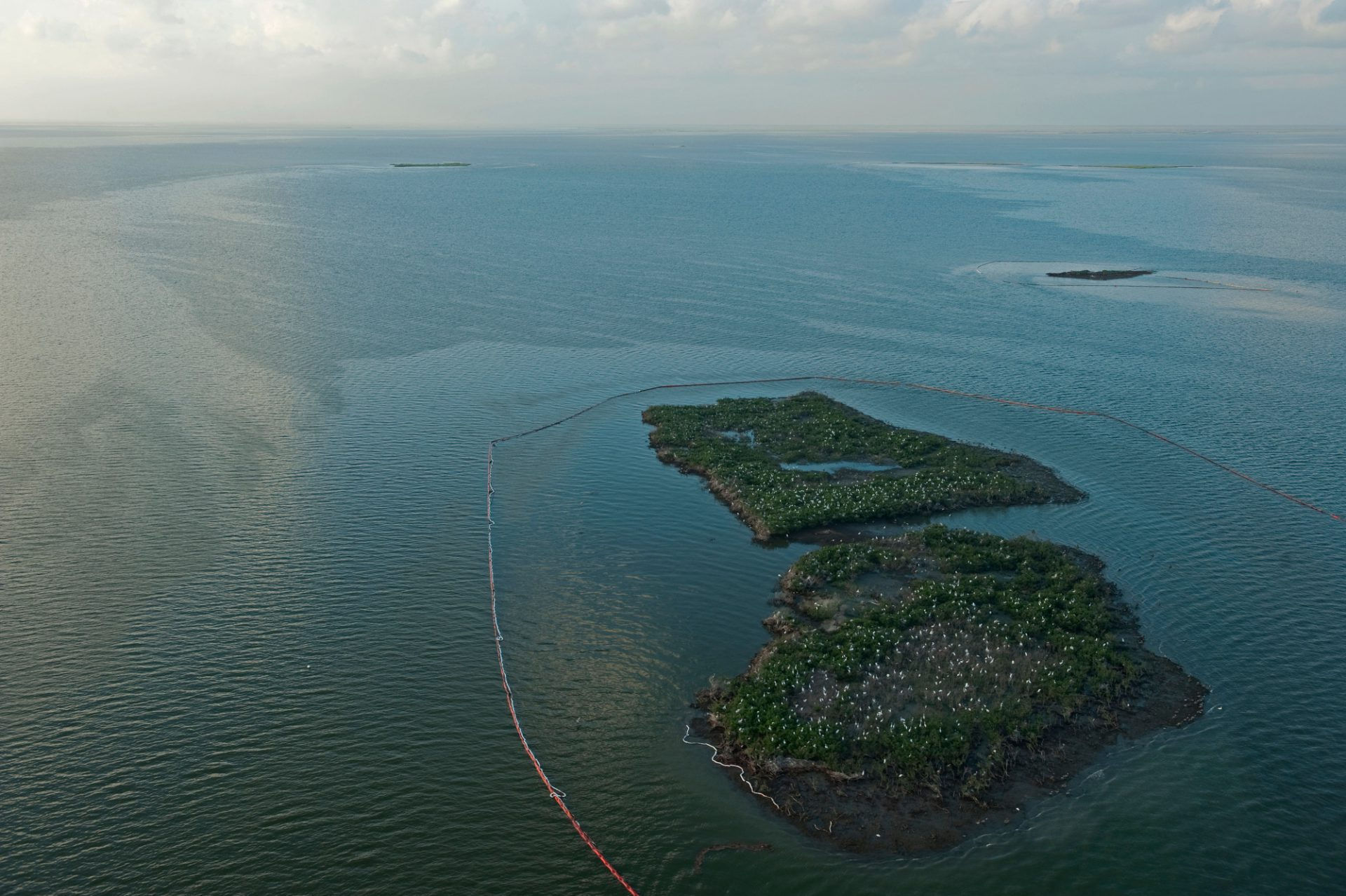 Photo: Oil booms ring Cat island to protect it from the Deepwater Horizon spill.