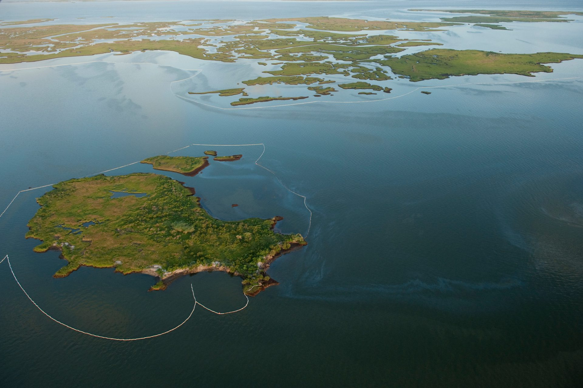 Photo: Aerial view of the oil booms deployed around Queen Bess Island in an attempt to protect it from the Deepwater Horizon spill.