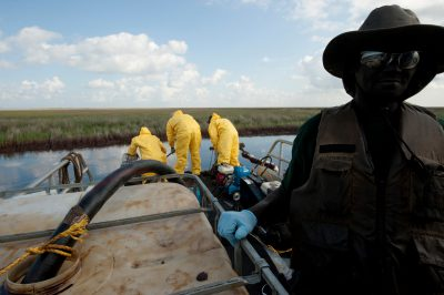 Photo: A crew of BP contractors attempt to siphon oil from the Deepwater Horizon spill out of a marsh in the Gulf of Mexico.
