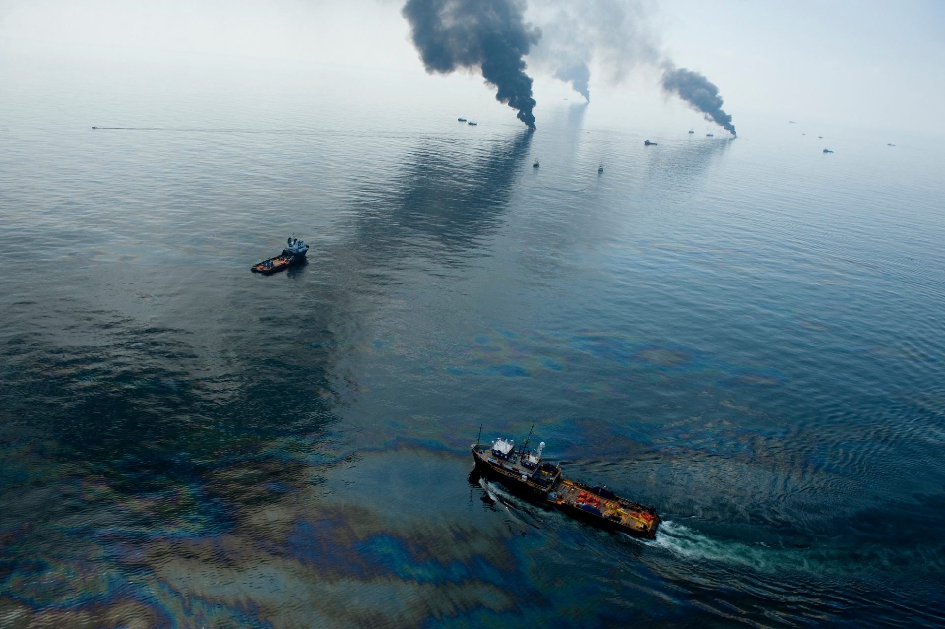 Photo: Boats burning off surface oil not near the Deepwater Horizon spill site creating huge black columns of smoke in the Gulf of Mexico.