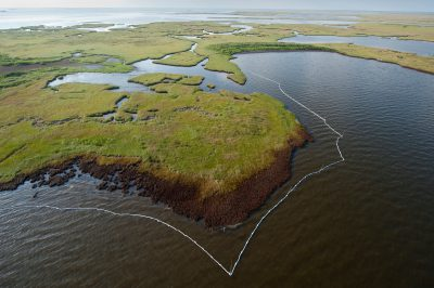 Photo: An aerial of heavily oiled marshlands surrounded by oil booms in Barataria Bay, Louisiana.