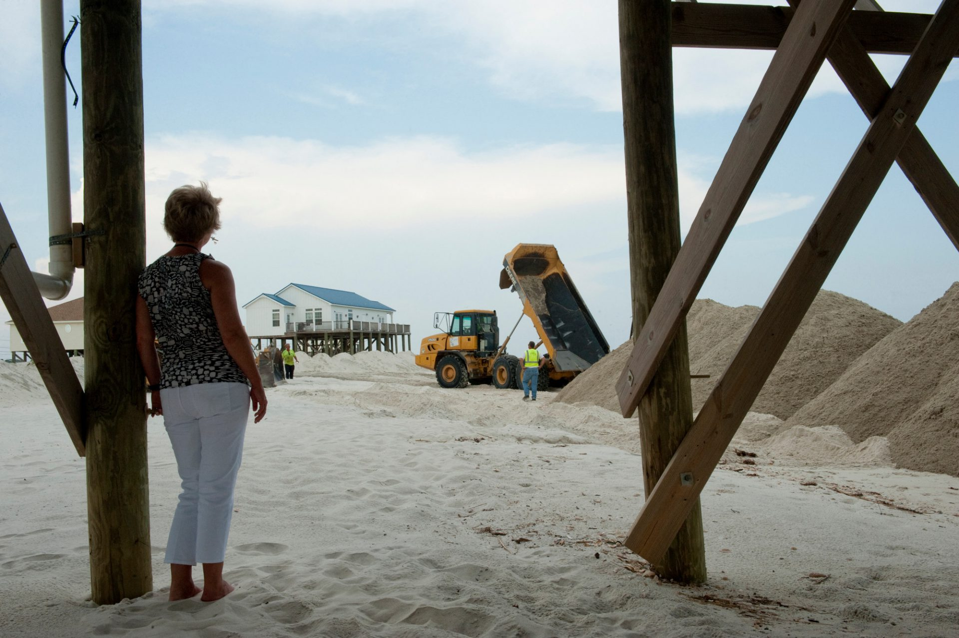 Photo: A woman stands beneath a home watching crews build new berms, with BP money, in order to protect the beaches from storm water and the oil from the deep water horizon spill that could come with it on Dauphin Island, Alabama.