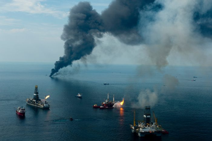 Photo: On board a PHI helicopter/media flight covering the deep water horizon oil spill at the spill site, two types of burning are now going on. The big black column of smoke is from oil being burned after being skimmed up with ships towing booms.