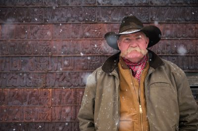 Photo: A man in a cowboy hat stands by a license plate covered barn during a snow storm.