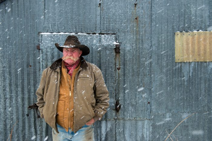 Photo: A man in a cowboy hat stands by a barn during a snow storm.