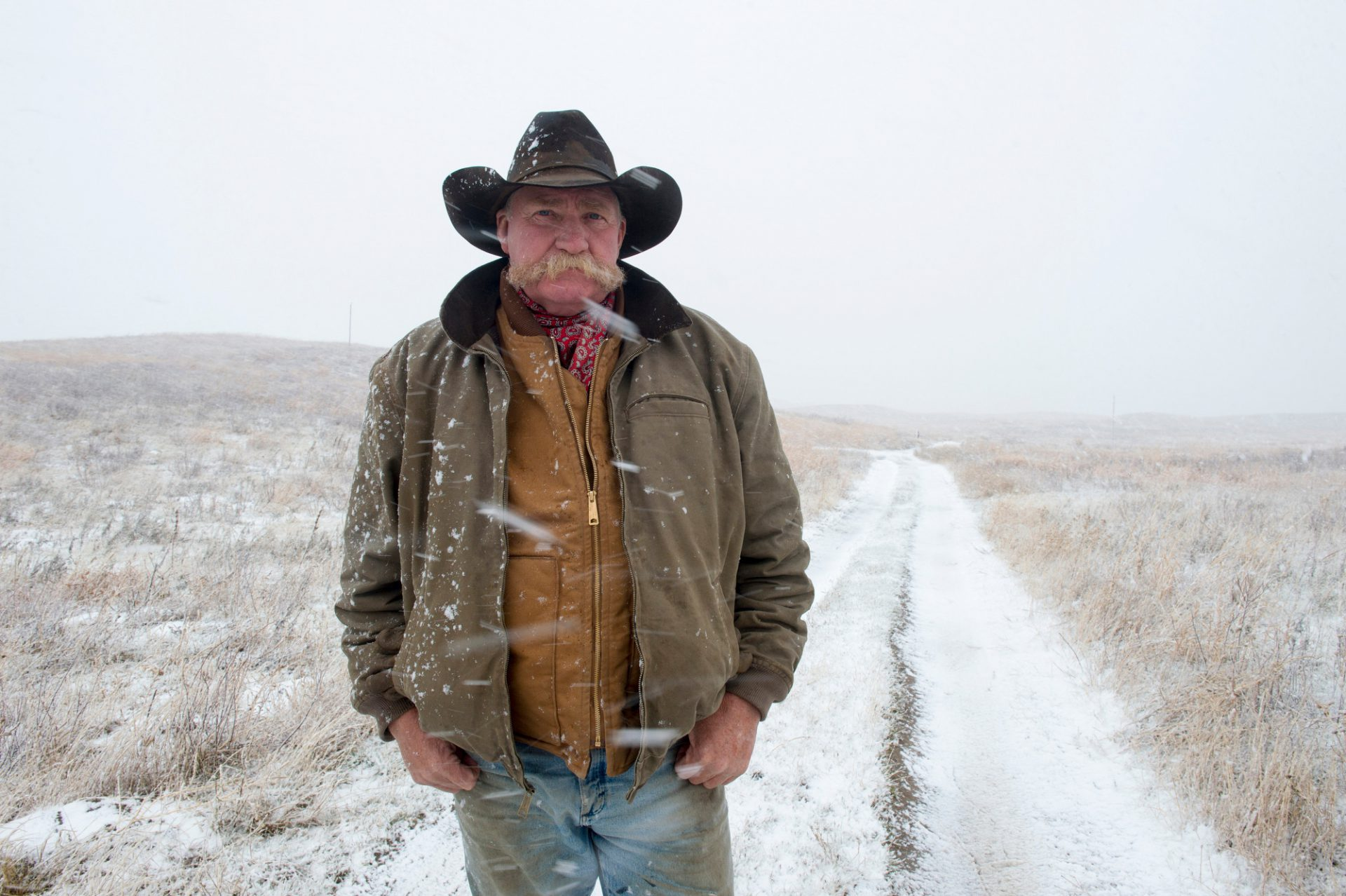 Photo: A man in a cowboy hat stands on a dirt road during a snow storm.