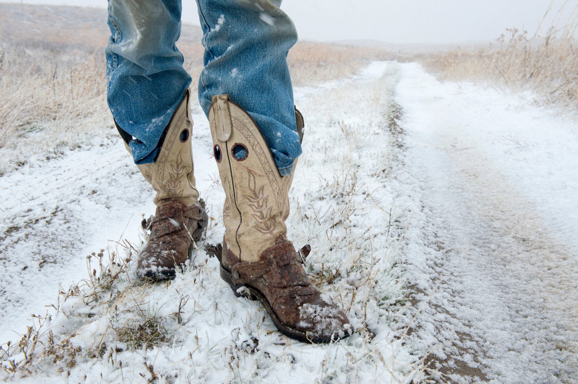Photo: A man in cowboy boots stands on a dirt road during a snow storm.