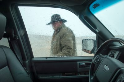 Photo: A man in a cowboy hat as seen through a vehicle window during a snowstorm.