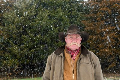 Photo: A man in a cowboy hat stands in front of evergreen trees during a snow storm.