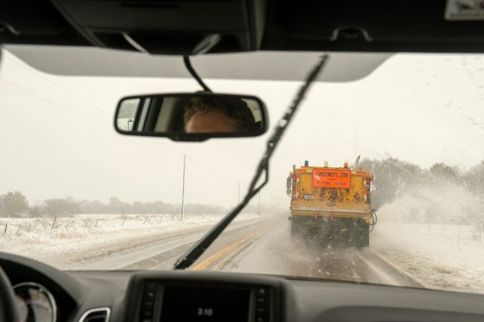 Photo: A bus drives on a snowy road behind a snowplow near Burwell, Nebraska.