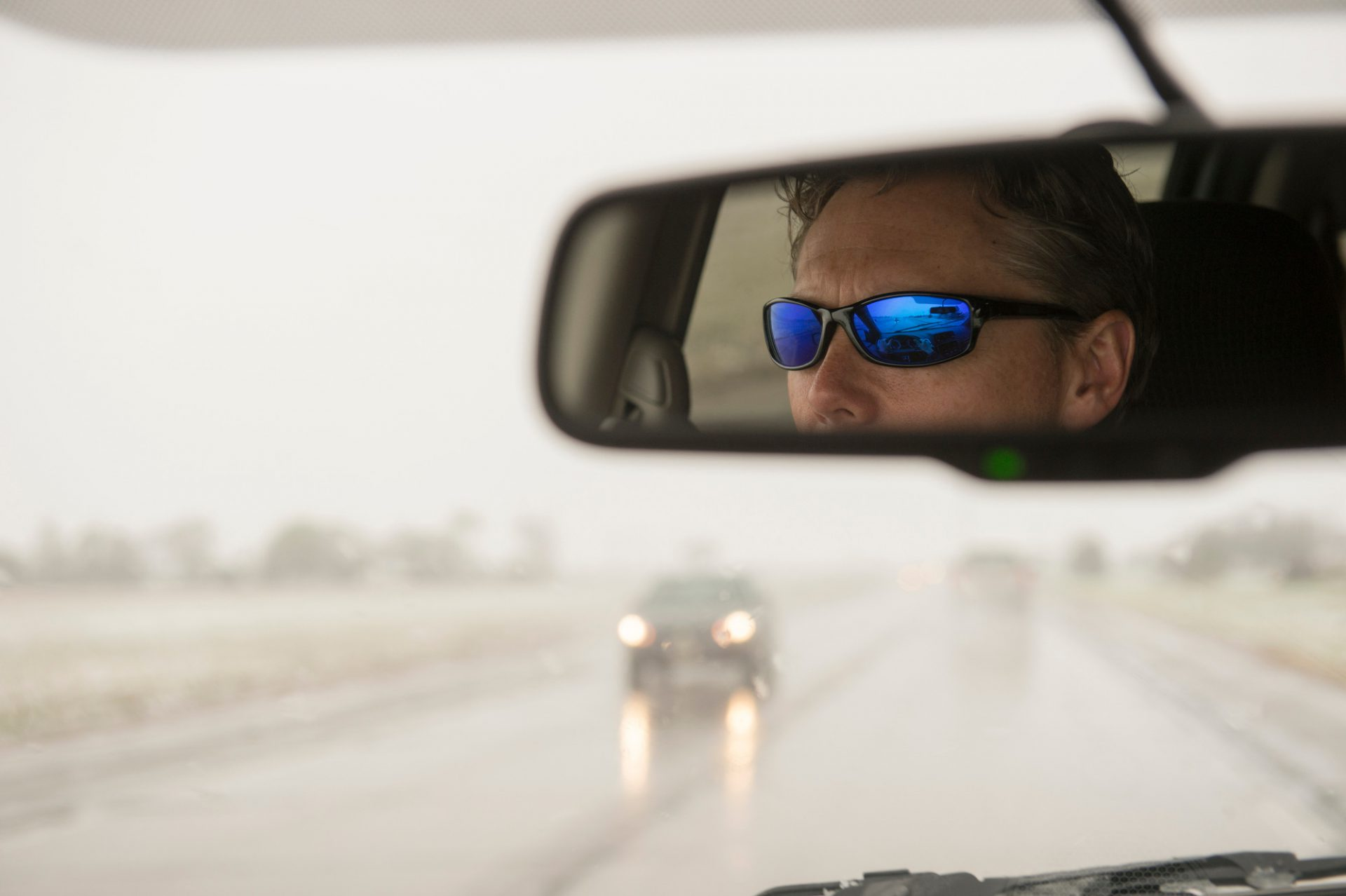 Photo: A man's reflection shows in the rear view mirror as he drives in winter weather conditions.